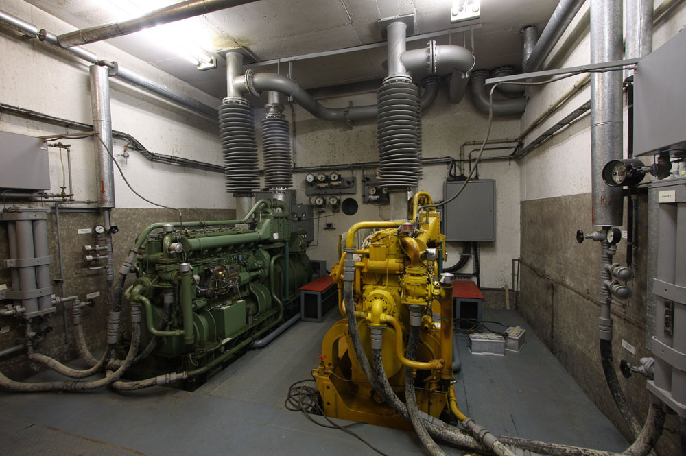 One of the few bunkers with the generators still intact. Note the small circular window in the back, to be able to view the generators from the plant room. As the generators were outside the gasprotected area the air could be contaminated, therefore visual inspection could be vital. This is a modern site with the generators standing on huge dampers, the whole floor is moving when you walk on it.